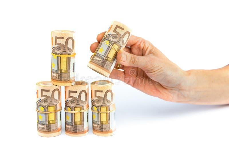 Hand die broodjes van euro nota's neerzetten stock foto