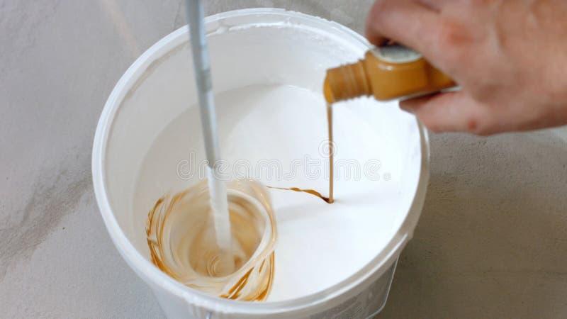 Hand die bruine vloeistof in emmer met witte verf gieten stock foto