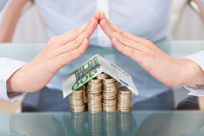 Hand die dak voor huismodel vormen dat van geld wordt gemaakt stock afbeeldingen
