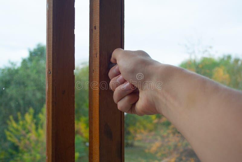 Hand, die das Fenster schließt stockbild
