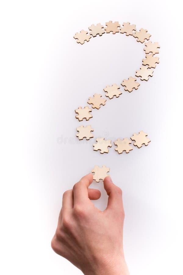 Hand, die das letzte Stück des Fragezeichens hält Fragezeichen gemacht von den Puzzlespielstücken auf weißem Hintergrund lizenzfreies stockfoto