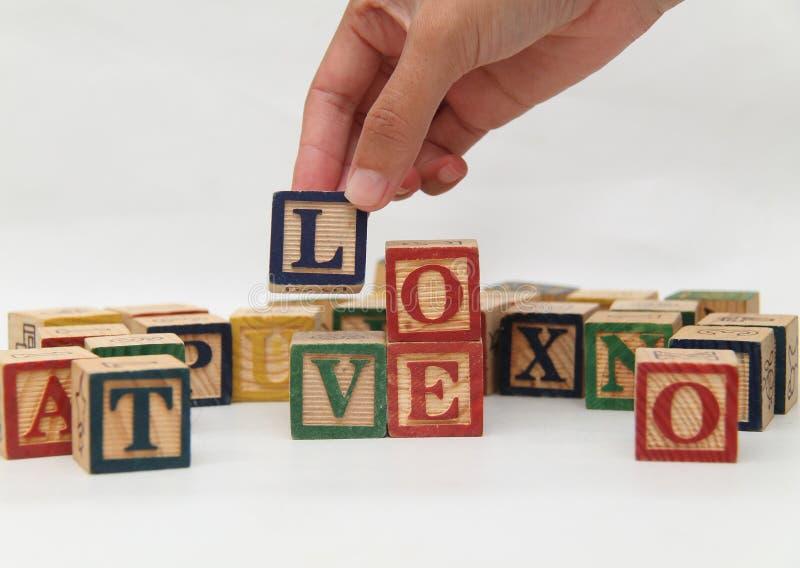 Hand die de brief houden, die de woord` liefde `, VERSIE 1 vormt stock afbeeldingen