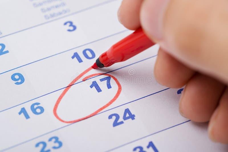 Hand die 17de datum op kalender merken stock foto's