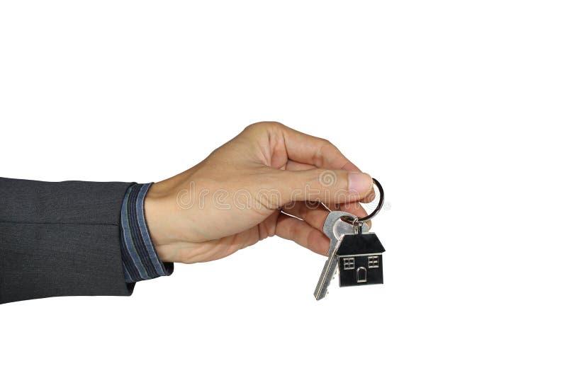 Hand die de huissleutel houden die op een witte achtergrond, met het knippen van weg wordt geïsoleerd stock afbeeldingen
