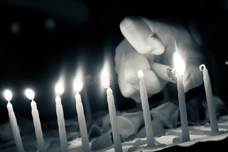 Hand die de kaarsen van de cake van de verjaardag met aansteker aanzet royalty-vrije stock afbeeldingen