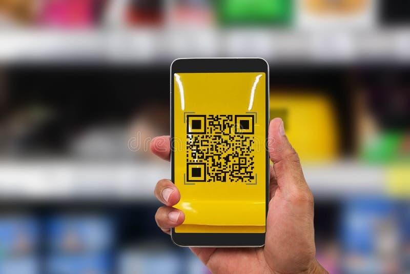 Hand die de mobiele code van het telefoonaftasten QR inzake vage goederen houden shel royalty-vrije stock fotografie