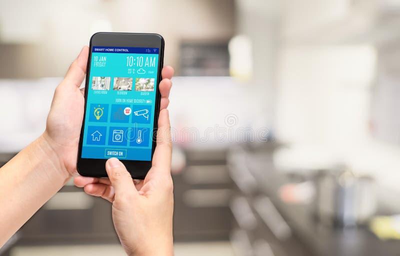 Hand die de mobiele controle mobiele app houden van het gebruiks slimme huis bij onduidelijk beeld BO stock afbeelding