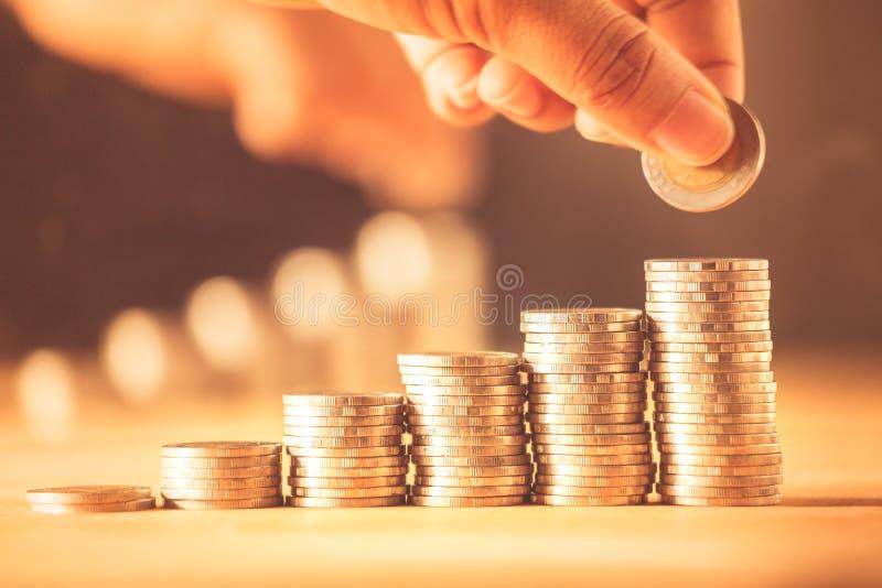 Hand die de stapel van geldmuntstukken voor sparen geldconcept zetten Het geldbeheer kweekt zaken royalty-vrije stock afbeeldingen