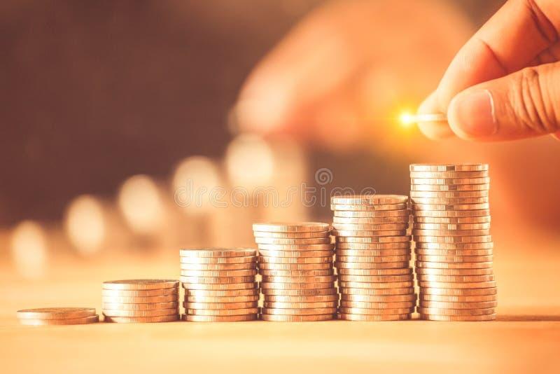 Hand die de stapel van geldmuntstukken voor sparen geldconcept zetten Het geldbeheer kweekt zaken stock fotografie