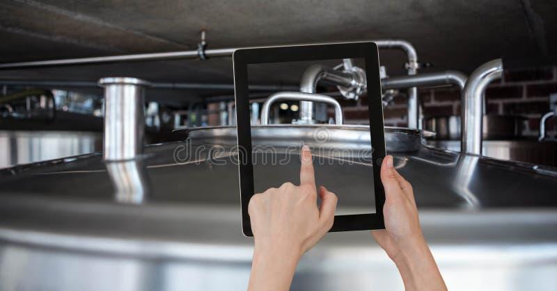 Hand die deksel van container fotograferen door digitale tablet bij brouwerij stock afbeelding