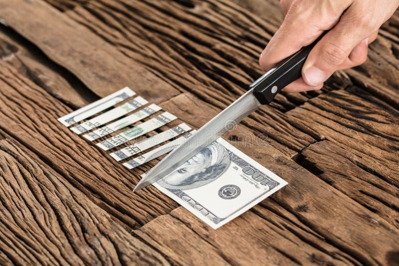 Hand, die den 100 Dollar Bill With Knife kürzt lizenzfreie stockfotografie