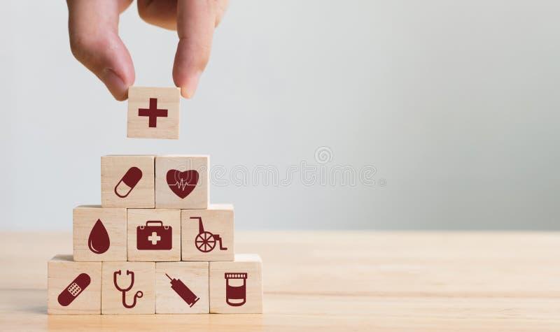 Hand, die den hölzernen Block stapelt mit dem Ikonengesundheitswesen medizinisch, Versicherung vereinbart lizenzfreie stockbilder