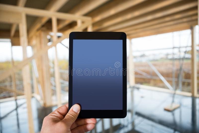 Hand, die Digital-Tablet mit leerem Bildschirm am Standort hält stockbild
