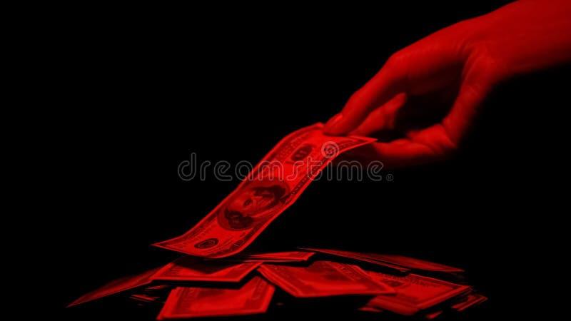Hand die die dollar van stapel nemen door rood licht, de bloedige beloning van de geldmisdaad wordt verlicht royalty-vrije stock afbeelding