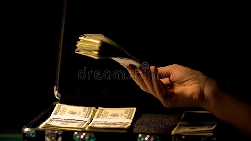 Hand die dollars in koffer, onwettige zaken controleren, witwassen van geld, terugslag stock afbeelding