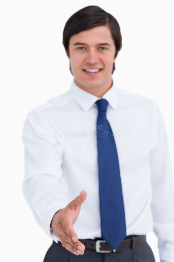 Hand die door glimlachende jonge kleinhandelaar wordt aangeboden royalty-vrije stock afbeeldingen