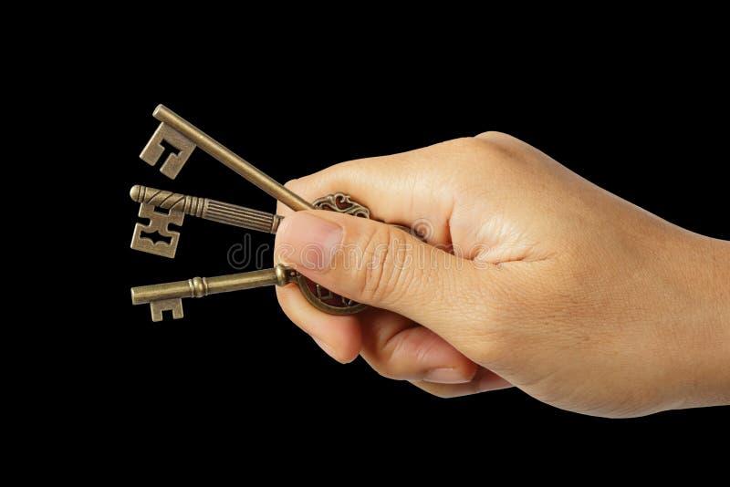 Hand, die dreifache Schlüssel lokalisiert auf Schwarzem mit Beschneidungspfad hält stockbilder