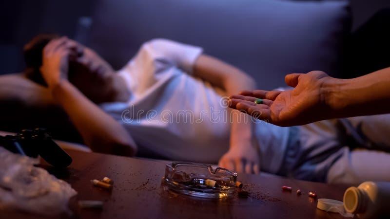 Hand die drug gewijde jonge mannelijke tablet, schadelijke gewoonte, clubdrugs aanbieden royalty-vrije stock afbeelding