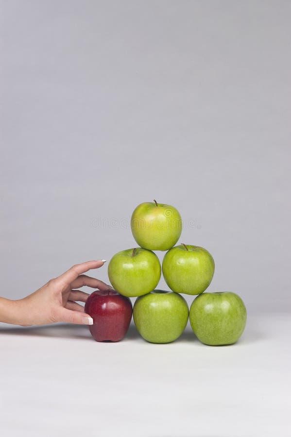 Hand die een appel van een stapel selecteren stock fotografie