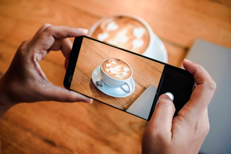 Hand die een beeld van hete de koffiekop van de lattekunst nemen met kunstschuim op houten lijst met haar smartphonezitting bij e stock foto