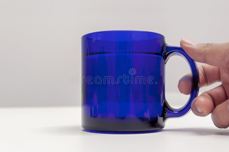 Hand die een blauwe kop thee houden stock afbeeldingen
