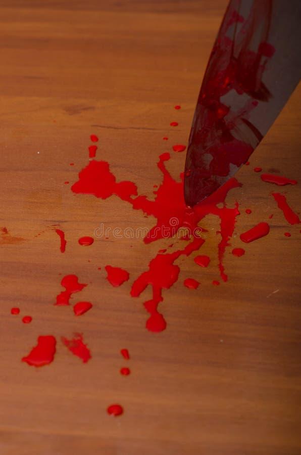 Hand die een bloedig mes houden stock afbeelding