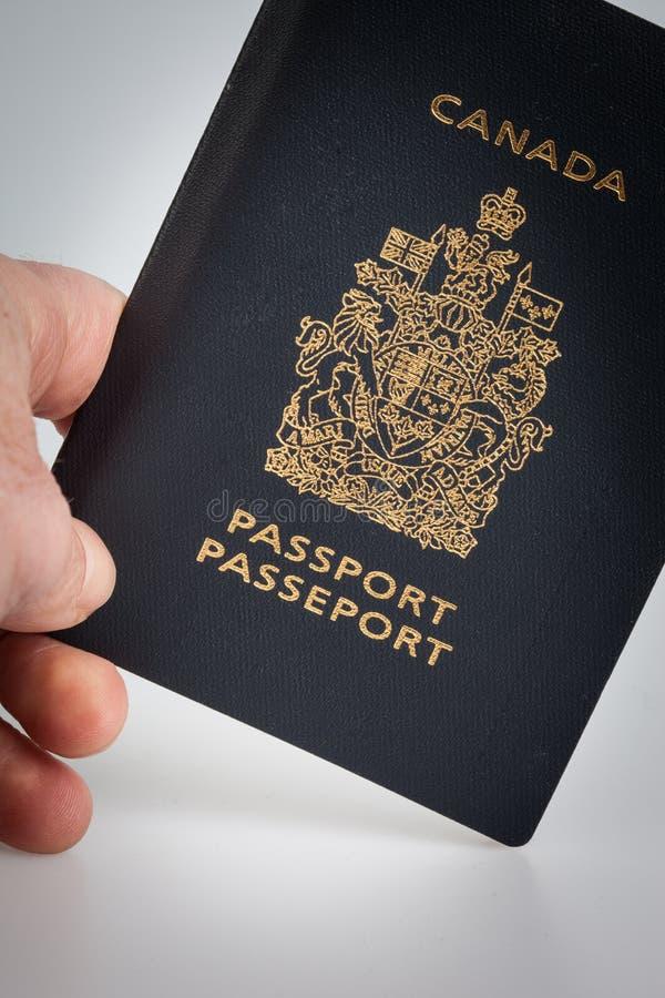 Hand die een Canadees paspoort houden stock afbeeldingen