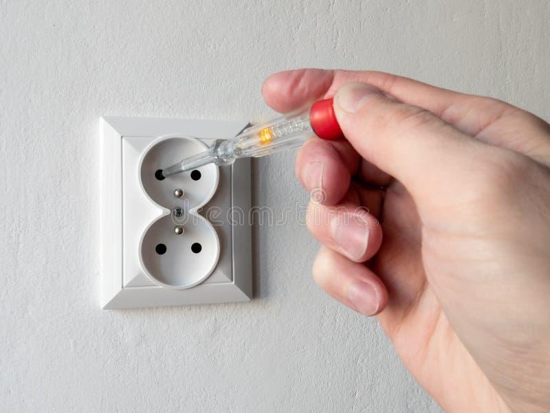 Hand die een elektriciteitsmeetapparaat houden en voltage in elektrische contactdoos controleren stock afbeeldingen