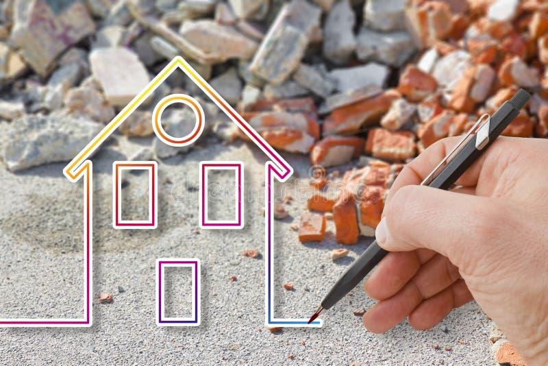 Hand die een gekleurd huis trekken tegen een beton en baksteenpuinpuin - het conceptenbeeld van de aardbevingswederopbouw stock foto's