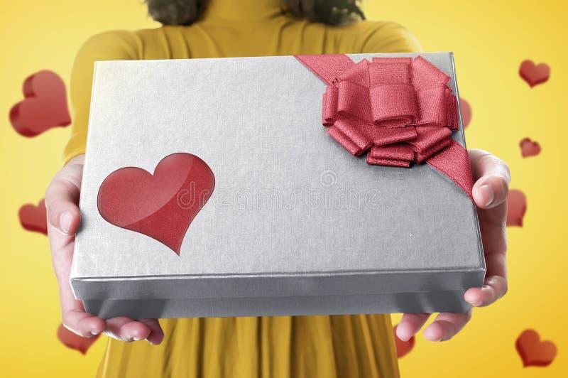 Hand die een giftdoos met rode lint en hartvorm voor mot houden royalty-vrije stock afbeelding