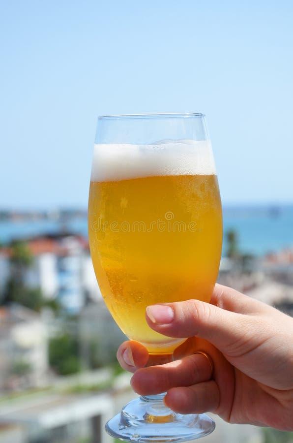 Hand die een glas bier op strand tropische overzeese achtergrond houden Het concept van de vakantievakantie royalty-vrije stock foto's