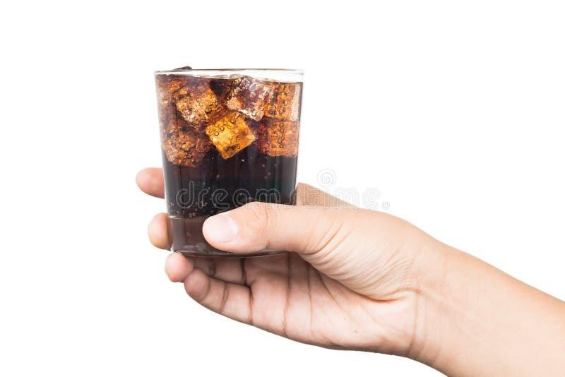 Hand die een glas van ijs gevulde koude en bruisende koladrank houden stock foto