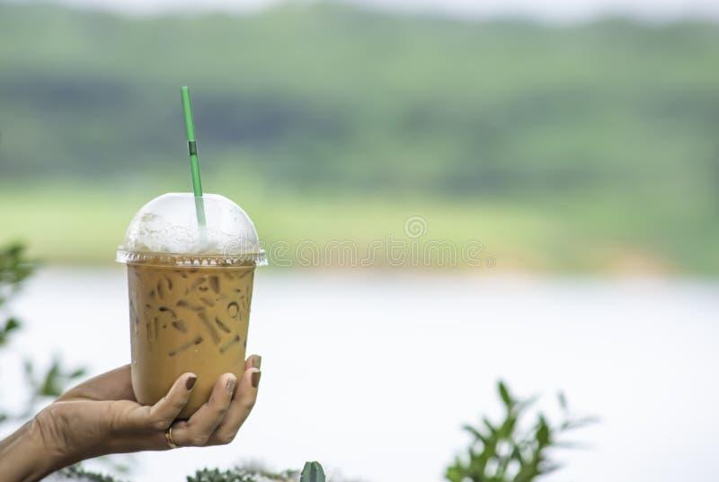 Hand die een glas van koud espresso Achtergrond onscherp meningenboom en water houden stock afbeeldingen