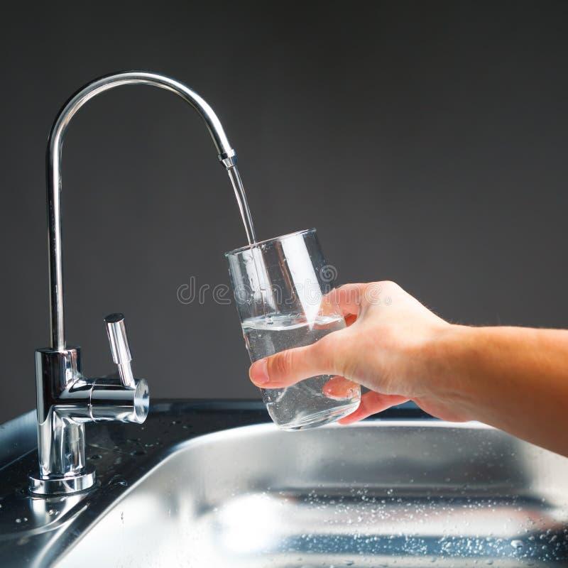 Hand die een glas water gieten stock afbeeldingen
