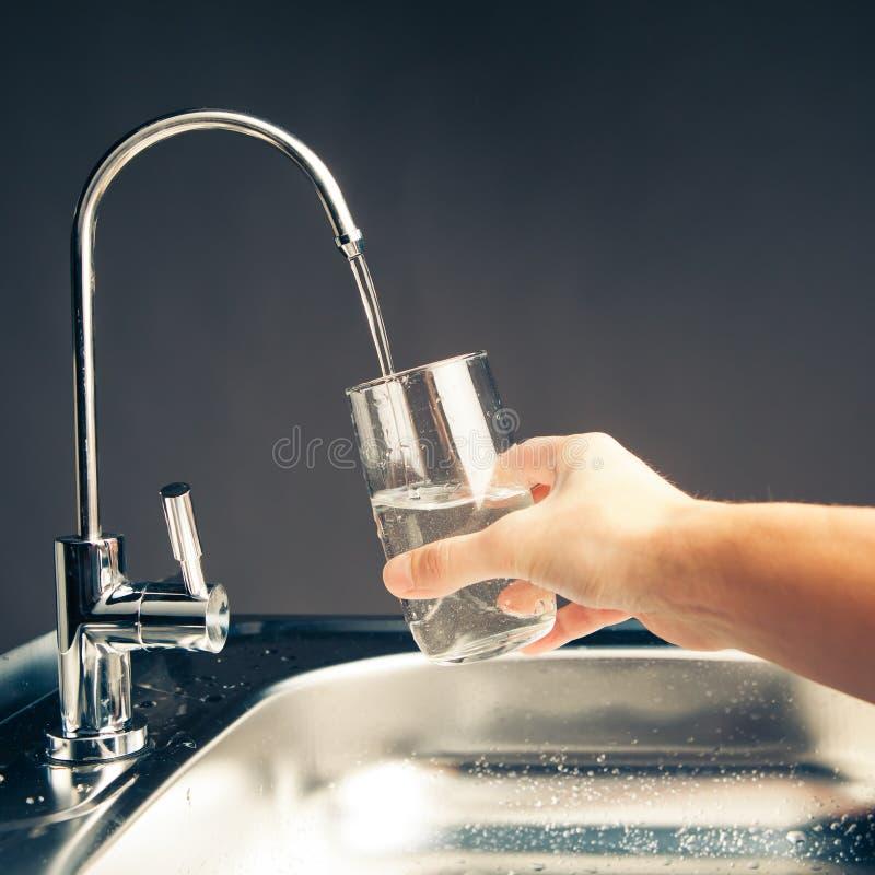 Hand die een glas water gieten royalty-vrije stock afbeelding