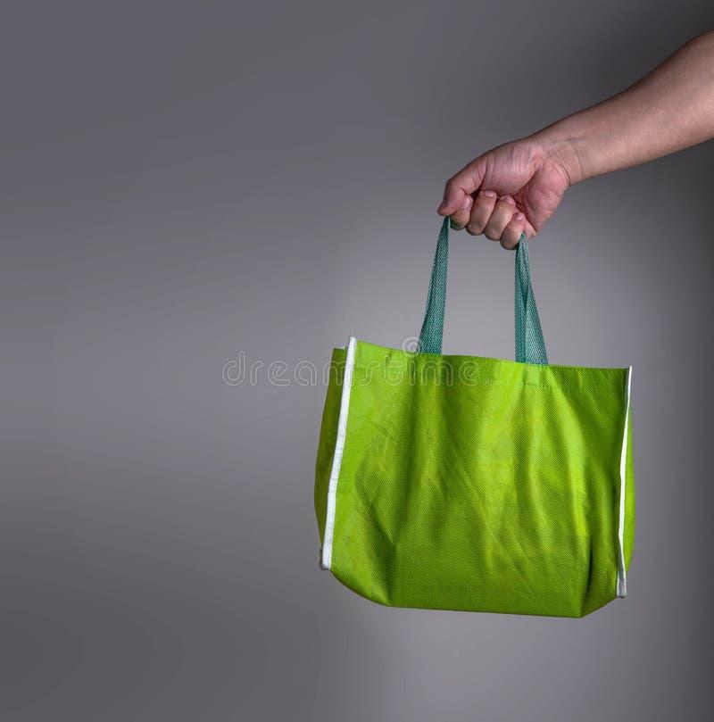 Hand die een groene kringloop groene zak, eco het vriendschappelijke winkelen o houden stock foto's