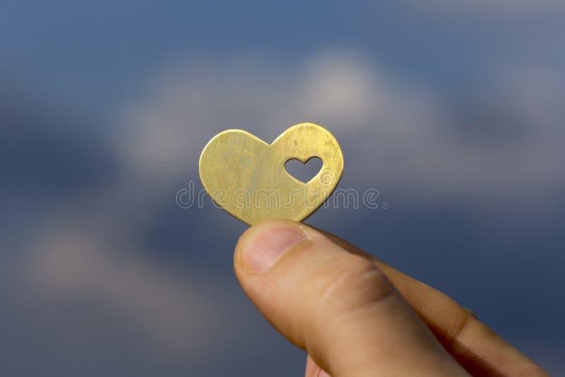 Hand die een Hart houden tegen de Blauwe Hemel stock foto
