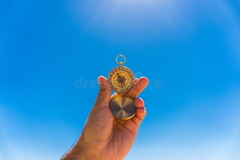 Hand die een kompas met blauwe hemelachtergrond houden Jonge volwassenen stock foto