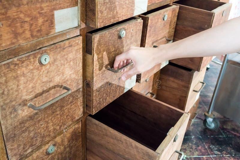 Hand die een lade van oud achtervolgd houten kabinet trekken royalty-vrije stock foto's