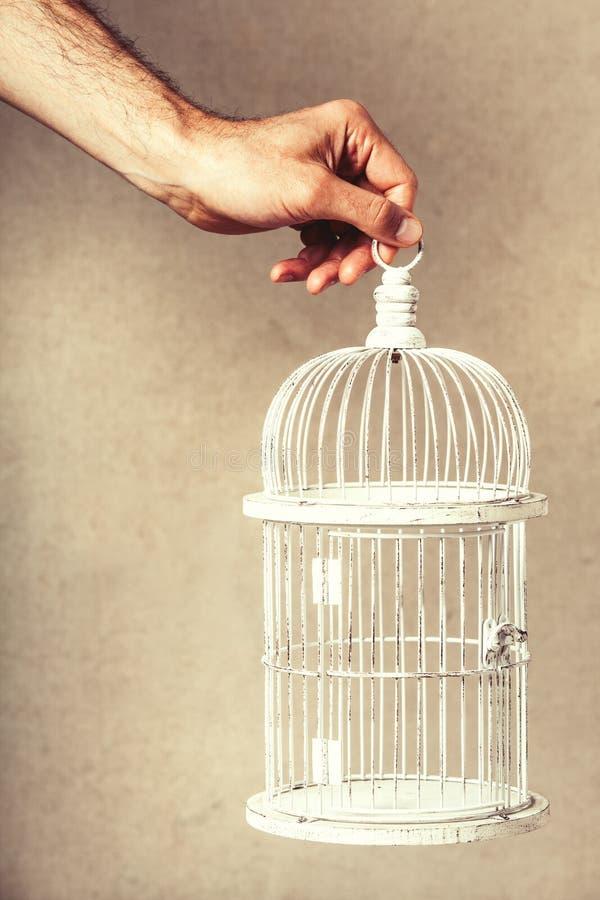 Hand die een lege kooi houden Ontbreken van ideeën en dromen Vrijheid en hoop stock foto