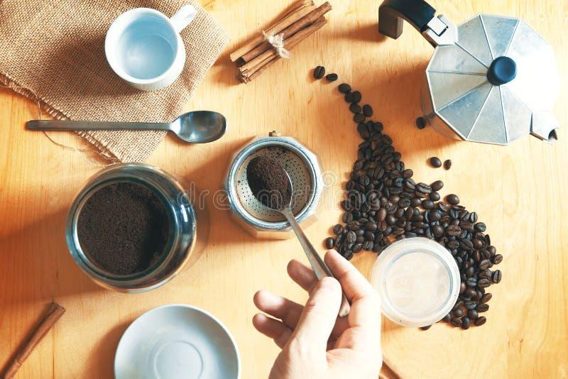 Hand die een lepel houden die één of andere espressokoffie met een koffiepot voorbereiden op een rustieke houten lijst Daarna, so royalty-vrije stock fotografie