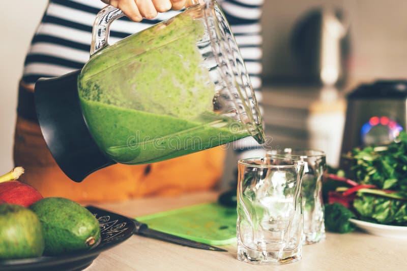 Hand die een mixerkom houden en groene smoothie gieten in een glas royalty-vrije stock afbeelding