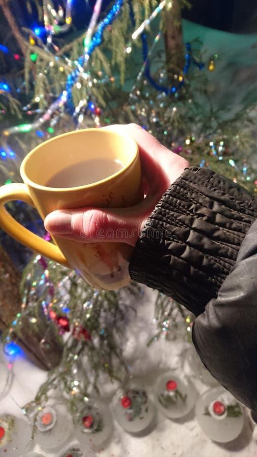 hand die een mok met een hete drank op de achtergrond van de Kerstboom in het nieuwe jaar houden stock afbeeldingen