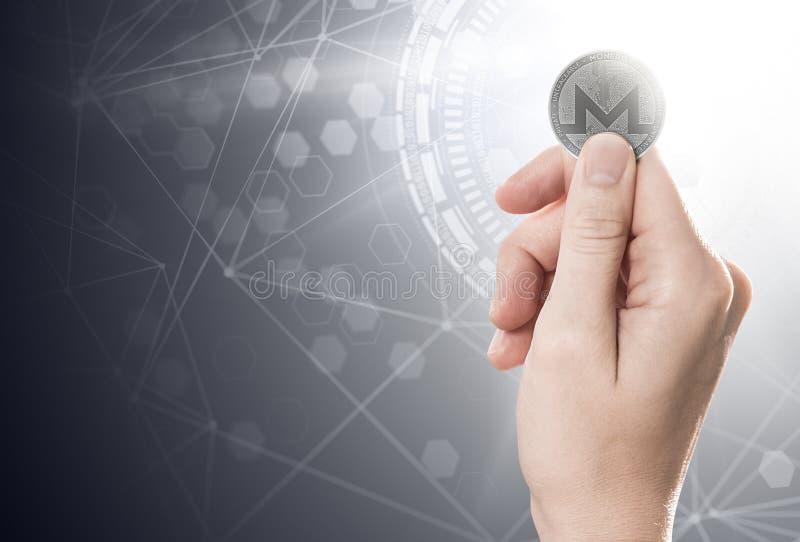 Hand die een Monero-muntstuk op een heldere achtergrond met blockchain houden royalty-vrije illustratie