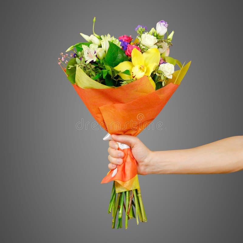 Hand die een mooi boeket van verschillende bloemen houden Geïsoleerde royalty-vrije stock afbeelding