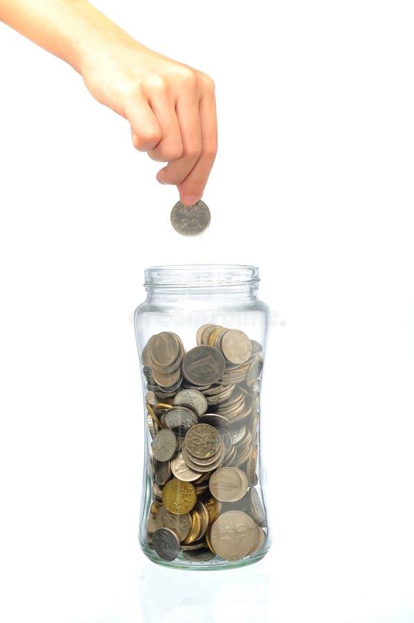 Hand die een muntstuk zetten in glasfles royalty-vrije stock foto's