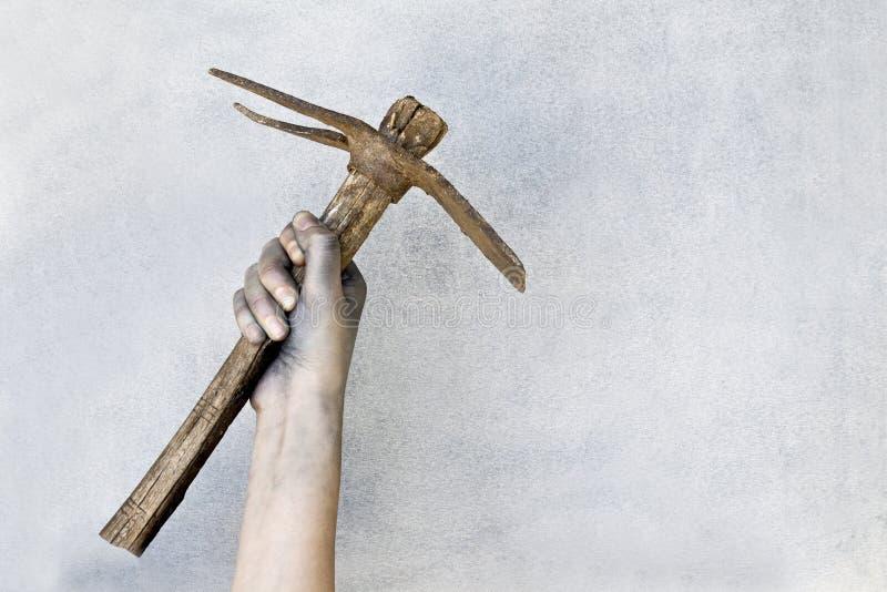Hand die een oude pikhouweel op grijze achtergrond houden stock foto's