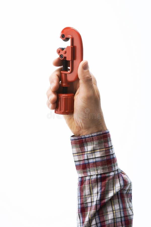 Hand die een pijpsnijder houden stock foto