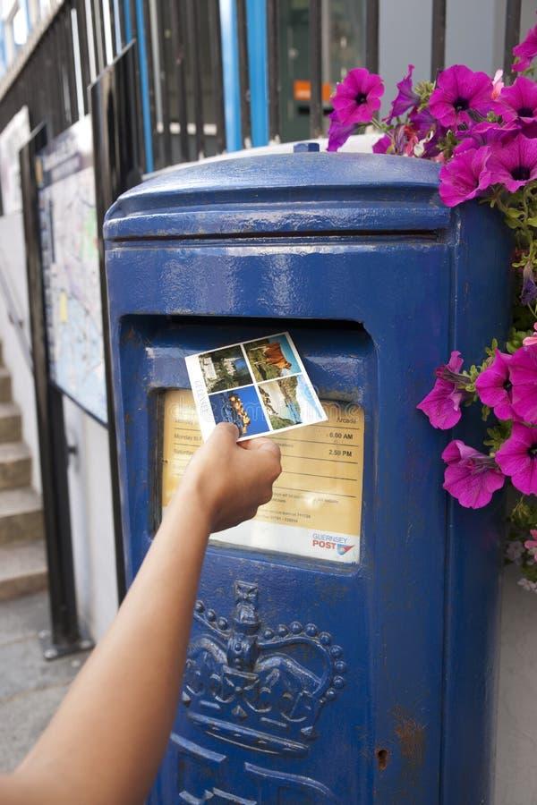 Hand die een prentbriefkaar in een Blauwe Guernsey-Postbus uniek aan Guernsey in de stad van St Pierre Port St Peter Port, de lei stock foto's
