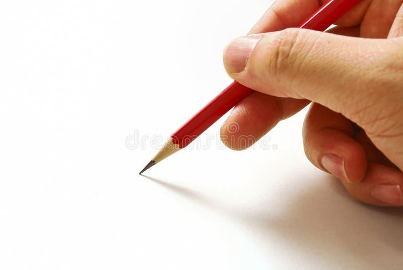 Hand die een rood potlood houdt dat op Witboek wordt geïsoleerd stock fotografie